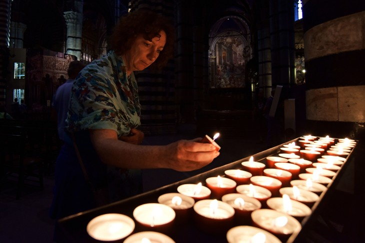 A woman places a votive candle on a rack in the Duomo di Siena on Wednesday, June 8 2016. Candles are lit and placed at alters as a part of prayer. (Photo by Rebecca Noble)