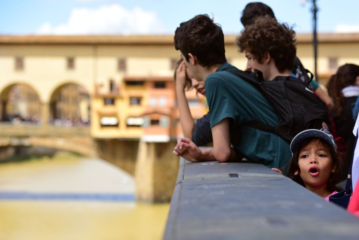 A girl gets her first glimpse of the Arno River behind the Ponte Vecchio bridge in Florence, Italy on Friday, June 17, 2016. The Ponte Vecchio bridge is the oldest bridge over the Arno River in Florence. (Photo by Rebecca Noble)