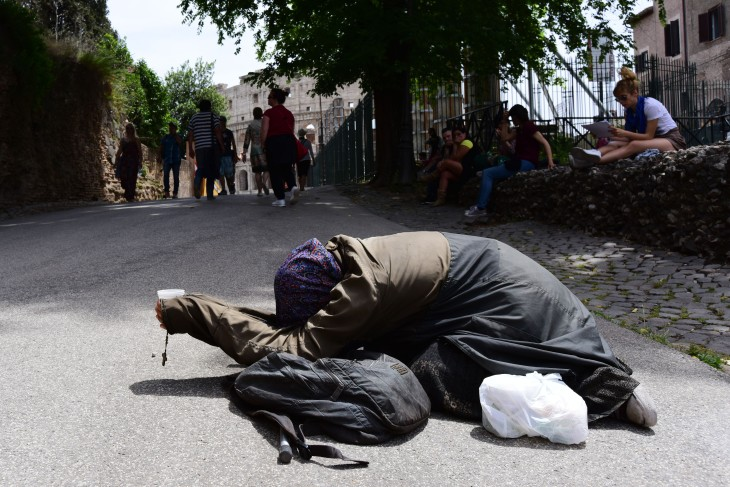 A beggar holding a rosary kneels on the sidewalk leading from the Roman Forum to the Coliseum in Rome, Italy on Friday, May 27, 2016. Homelessness rates increased dramatically after the Italian economic crisis and the number of homeless people in Rome was estimated to be 48,000 in 2014. (Photo by Rebecca Noble)